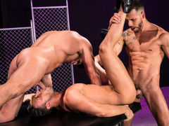 Naked except for their ebony leather boots, three horny men indulge their primal urges. Hairy bodybuilder Bruce Beckham and tatted FX Rjos stand over smooth Josh Conners, who is crouching with his spread waste cheeks in the air. Bruce and FX take turns ri