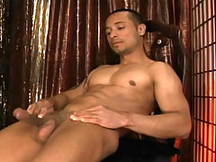 Sexy black stud jerking off around a chair showing his butt